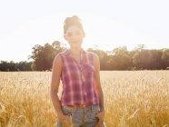 Jovem mulher em pé no campo de plantas de milho alto em luz suave . — Fotografia de Stock