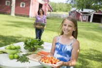 Girl carrying bowl of freshly picked cherries at garden table. — Stock Photo