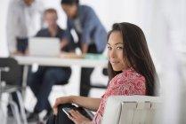 Азиатка отдыхает на офисном диване с коллегами с помощью ноутбука в фоновом режиме . — стоковое фото