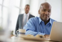 Man sitting at desk and using laptop with coworker in background. — Stock Photo