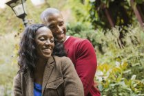 Smiling man and woman hugging each other in garden. — Stock Photo