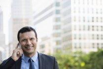 Vista frontal do empresário falando por telefone na rua urbana . — Fotografia de Stock