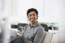Young businessman smiling and holding digital tablet in office armchair. — Stock Photo