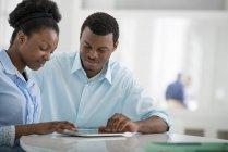 Homme et femme assis côte à côte et utilisant une tablette numérique au bureau . — Photo de stock