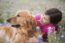 Elementar de idade menina abraços retriever dourado animal de estimação ao ar livre — Fotografia de Stock