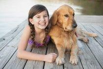 Pré-adolescente em trajes de banho com cão retriever dourado deitado no cais — Fotografia de Stock