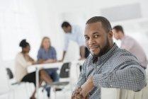 Середина взрослого мужчины, оглядывающегося через плечо в офисном интерьере и коллеги по встрече . — стоковое фото
