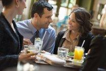 Hombre y la mujer sentada en bar con bebidas y charlando - foto de stock