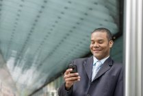 Businessman in suit standing on street, smiling and using smartphone. — Stock Photo