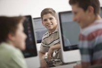 Vorpubertäre Jungen sitzen im Computerlabor mit Reihen von Computermonitoren. — Stockfoto