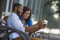 Coppia seduta sulla panchina e scattare selfie in città . — Foto stock