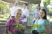 Filles tenant de jeunes plantes dans des pots avec un couple mature et une jeune femme en arrière-plan à la ferme . — Photo de stock