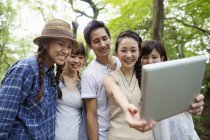 Gruppe von asiatischen Freunden nehmen Selfie mit digital-Tablette im Wald. — Stockfoto