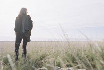 Woman carrying jacket and backpack standing in grassland, rear view. — Stock Photo