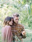 Young couple standing by apple tree in orchard and holding apple. — Stock Photo