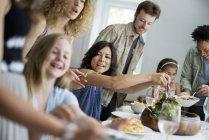 Famille d'adultes et d'enfants recueillant autour de table — Photo de stock
