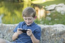 Elementary age boy sitting by water and using handheld electronic game. — Stock Photo