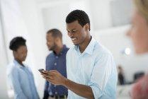 Hombre usando teléfono inteligente en el interior de la oficina con personas de pie . - foto de stock