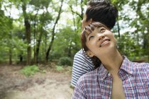 Young woman leaning on man shoulder and looking up in forest. — Stock Photo