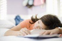 10-13 Mädchen schläft auf Bett mit Schulbuch — Stockfoto