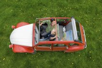 Overhead view of mature couple in car with roof open. — Stock Photo