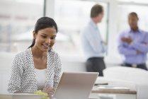 Junge Frau sitzt am Schreibtisch und Laptop im Büro mit Kollegen im Hintergrund verwenden — Stockfoto