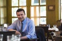 Uomo che si appoggia sul tavolo e guardare a porte chiuse in bar interni. — Foto stock