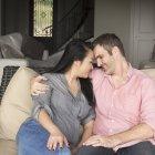 Улыбающиеся мужчина и женщина сидят на диване, обнимаются и смотрят друг на друга. . — стоковое фото