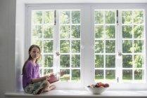 Menina idade elementar sentado no peitoril da janela com tigela de frutas e livro de leitura . — Fotografia de Stock