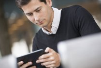 Close-up of young man sitting on street and using digital tablet. — Stock Photo