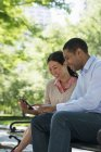 Mid adult man and woman using digital tablet together in city park. — Stock Photo