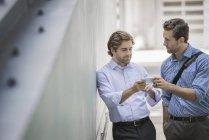 Dois homens de negócios em pé na rua urbana e compartilhamento de smartphones . — Fotografia de Stock