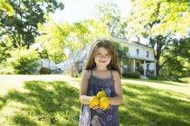 Kleines Mädchen im Garten mit gelben Zitronen in der Hand. — Stockfoto
