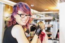 Колорист волос в перчатки, улыбаясь в камеру при применении краски красные волосы светлые волосы клиента. — стоковое фото