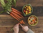 Cortada a exibição de legumes frescos de corte de pessoa na mesa de madeira — Fotografia de Stock