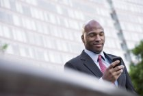 Low angle view of mid adult businessman using smartphone in city. — Stock Photo