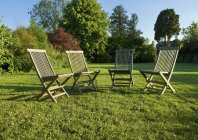 Garden chairs placed on green lawn in Gloucestershire in summer. — Stock Photo