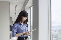 Jeune femme d'affaires japonaise utilisant une tablette numérique dans un immeuble de bureaux . — Photo de stock