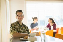Young man sitting at coffee shop counter with women talking in background. — Stock Photo
