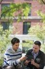 Männlichen Freunden teilen digital-Tablette während der Sitzung im Stadtpark — Stockfoto
