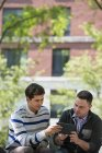 Male friends sharing digital tablet while sitting in city park. — Stock Photo