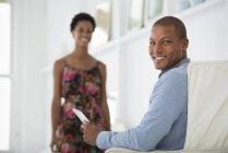 Junger Mann im Sessel sitzen und halten digital-Tablette mit Frau im Hintergrund — Stockfoto