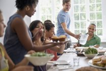 Group of men and women gathering around dining table and sharing meal. — Stock Photo