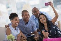 Жизнерадостная женщина берет selfie с друзьями с смартфон на вечеринке — стоковое фото