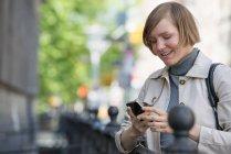 Середині дорослу жінку в куртці за допомогою смартфона в місті. — стокове фото