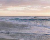 Waves and surf by sandy beach at dusk. — Stock Photo