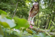 Preschooler girl playing with fishing net at pond in forest. — Stock Photo