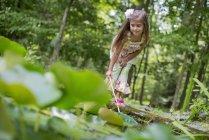 Дошкольница, играющая с рыболовной сетью у пруда в лесу . — стоковое фото