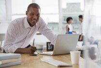 Young man using laptop while leaning on desk in office with coworkers in background. — Stock Photo