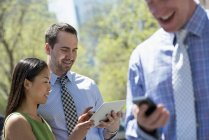 Businessman checking smartphone with couple sharing digital tablet in city park. — Stock Photo